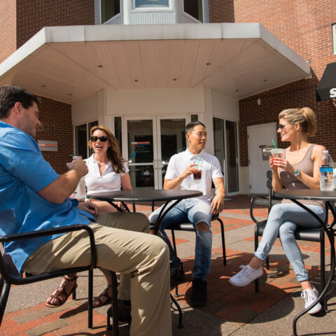 group of friends sitting at tables outside of Apartment in Wilmington DE